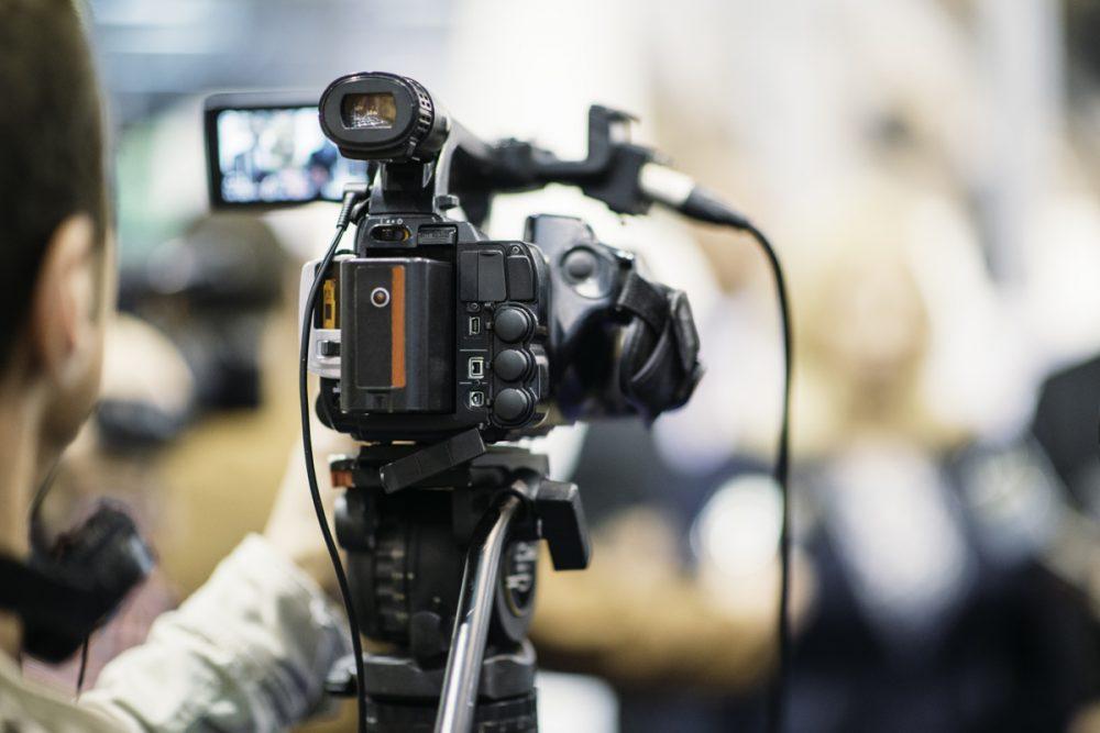 Television camera recording publicity event. Camera in focus, operator and event blurred